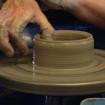 close up image of hands throwing a pot on the potter's wheel at eastnor pottery & the flying potter