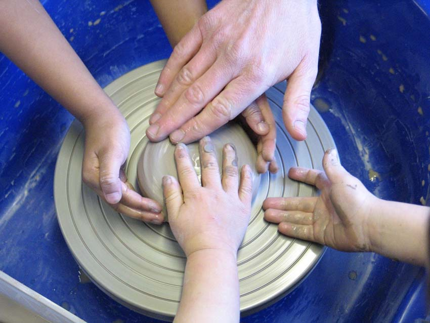 children and adult make pottery together on a potter's wheel