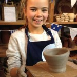 young girl uses the potters wheel to make a pot at eastnor pottery