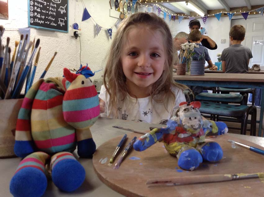girl makes a clay model of her cuddly toy at eastnor pottery nr Malvern hills