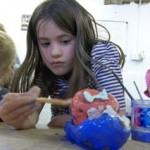 birthday girl paints her clay model at her birthday party at eastnor pottery herefordshire