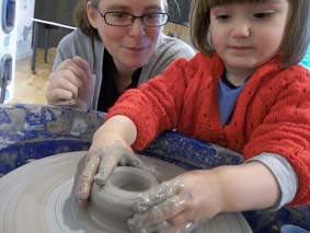 mum watches young potter experience the potter's wheel at moonbeams 3 exhibition at MAC birmingham