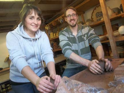 Swedish ceramics student erika and her boyfriend help wedge clay for pottery course participants at eastnor pottery herefordshire