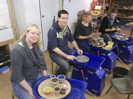four talented pottery workshop participants sample the delights of the p[otter's wheel at eastnor herefordshire