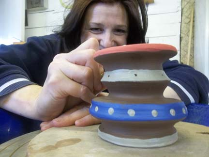 course participant karen decorates the pot she made on the potter's wheel