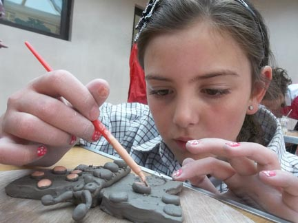 student at church lench first school painting her clay butterfly ready for voices and visions school exhibition in worcester cathedral