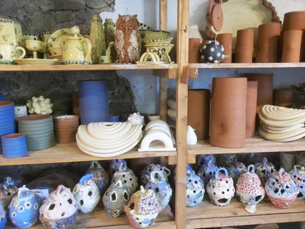Interesting shelves packed full of creative clay work and fired ceramic art