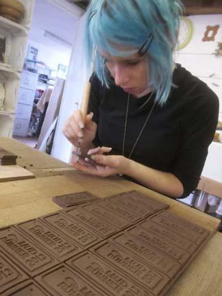 Lottie piercing holes into Mud Runner medals at Eastnor Pottery