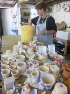 Workshop participants pots being glazed at Eastnor Pottery by pottery employee