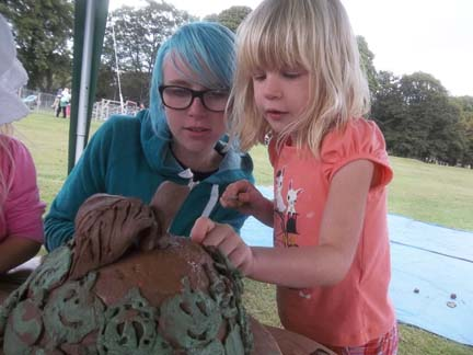 Lottie from Eastnor Pottery helps visitor make a giant Hfds cider apple