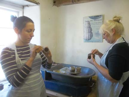 Mother & daughter make pottery on the potter's wheel at Eastnor Pottery in Herefordshire