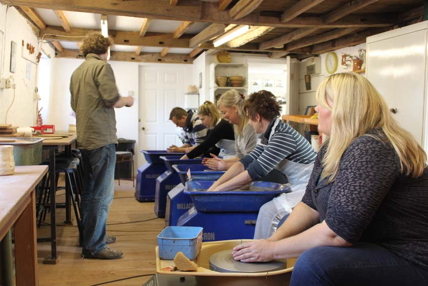 Marketing team learn how to make pots on the potter's wheel