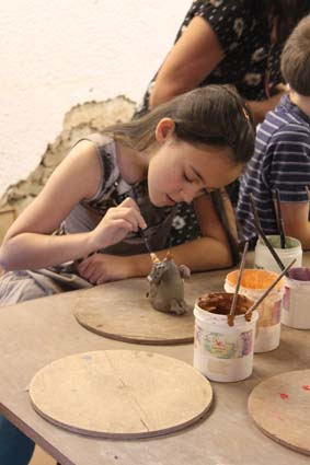 birthday girl painting a clay model