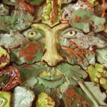Pottery tiles made by school children in Herefordshire in the shape of the green man
