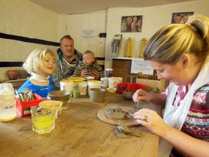 This family made baby hand prints and attached them to a clay pot made on the potter's wheel