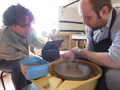 Jon the potter recording Ash from Ludicrooms make a pot on the potters wheel