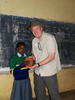 Mr Lewis presenting collaborative terracotta to school in Tanzania
