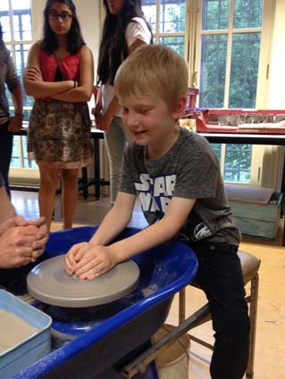 Child has a go on the potter's wheel at Festival of Cultures at King Edwards