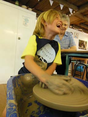 young potter spinning clay on the potter's wheel