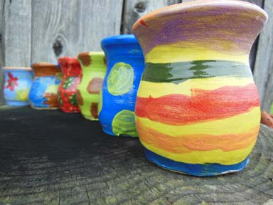 Pots made on the potter's wheel painted by staff at Brearley & Teviot Nursery School Birmingham as part of a clay team day