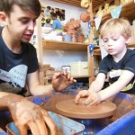 Child making a pot on the pottery wheel under the guidance of Ethan the potter