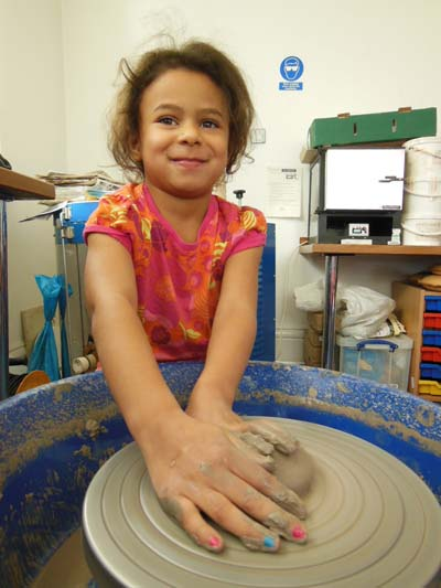 Girl making pottery on the potter's wheel in Bilston Craft Gallery