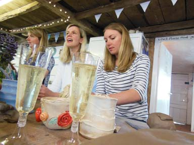 Girls enjoying a glass of prosecco as they make pottery at a hen party in Herefordshireo