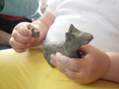 Young Hands Making Clay Dog