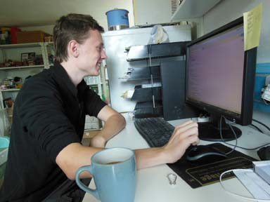 Jack working at the computer for apprenticeship with Eastnor Pottery