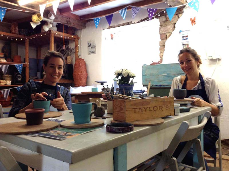 Pottery students painting brilliant pots