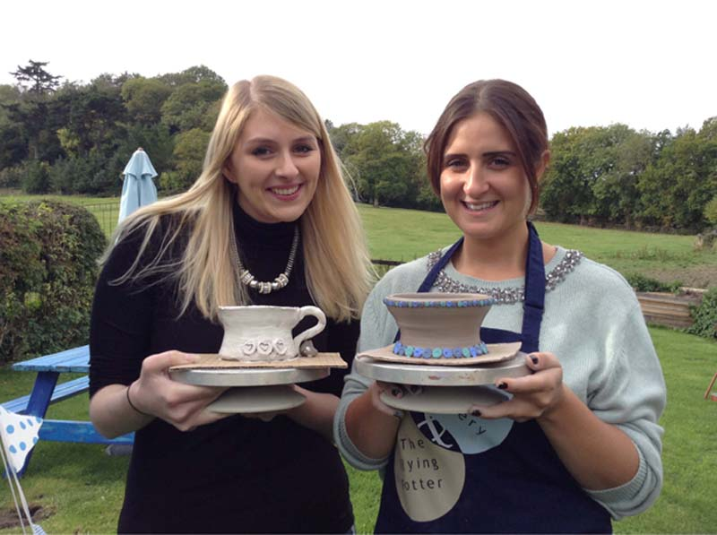 Two happy girls with brilliant pottery pieces at Eastnor