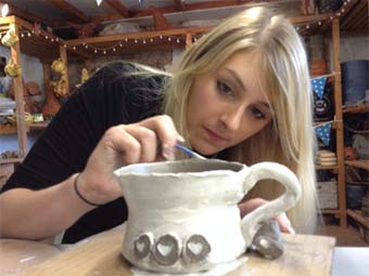 Carefully painting a magnificent pot at Eastnor Pottery