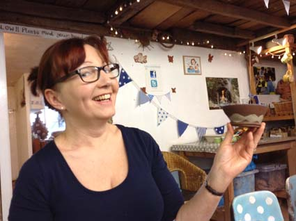 lady pleased with pottery creation made on the potter's wheel