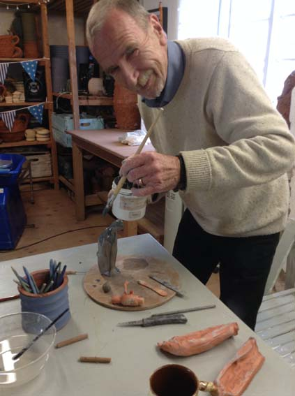Adding paint at Eastnor Pottery to clay figures made by mixed media artist