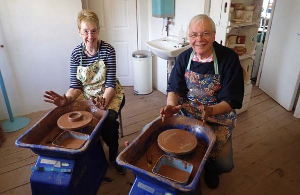 Potter's Wheel Workshop Participants at Eastnor Pottery learning new skill throwing clay