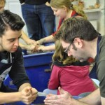 Eastnor Pottery's Apprentice Ethan teaching customer how to throw on the Potter's Wheel