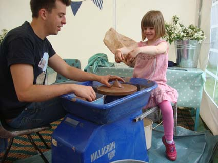 girl making a pot on the potter's wheel as part of her pottery birthday party in Eastnor