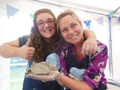 a couple of pottery hen party participants display their clay pots