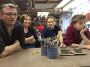 family watch their son make a pot on the potter's wheel
