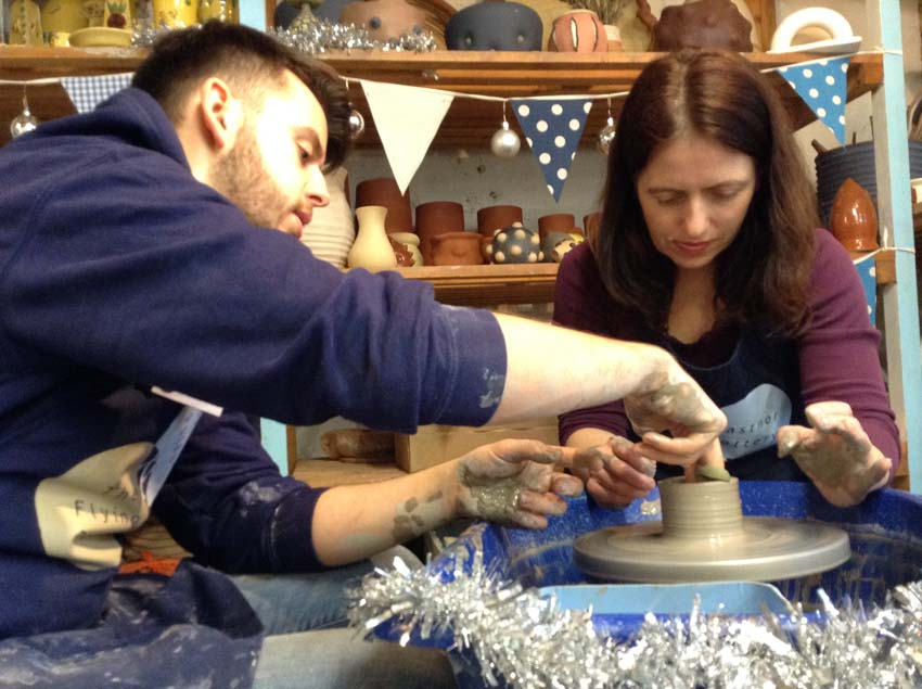 Visito at free potter's wheel event makes a pot under the guidence of potter Ethan from Eastnor Pottery