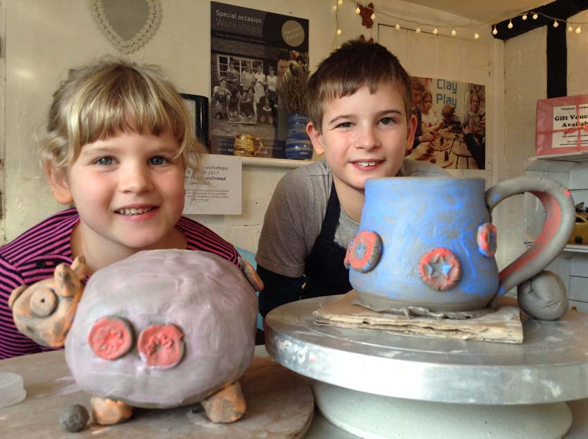 A brother and sister make a pottery piggy bank and wheel thrown mug at Eastnor Pottery as their Christmas present