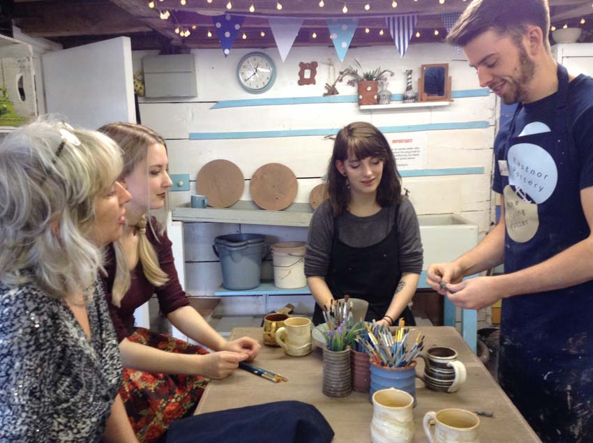 Ethan from eastnro Pottery demonstrates handles to birthday group