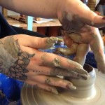adult hands on clay at eastnor pottery