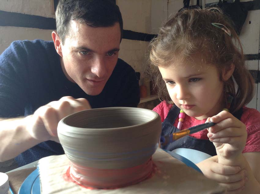 Father and daughter decorate a freshly thrown pot together