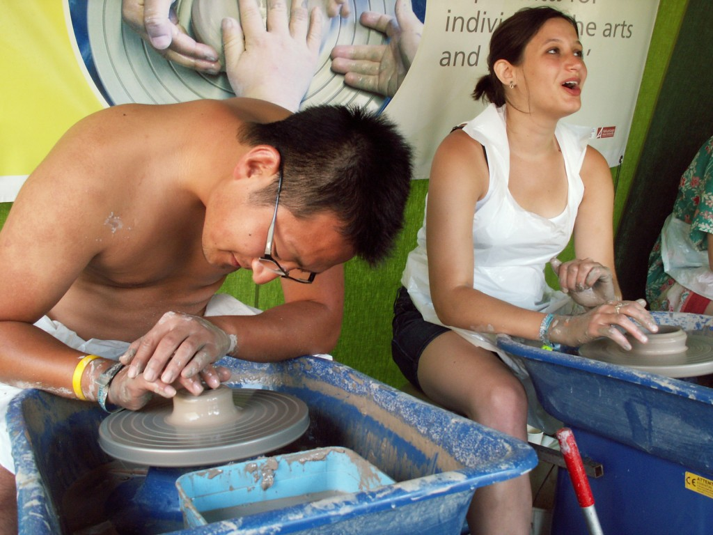 festival goers enjoy making pots on the potter's wheel at music festivals
