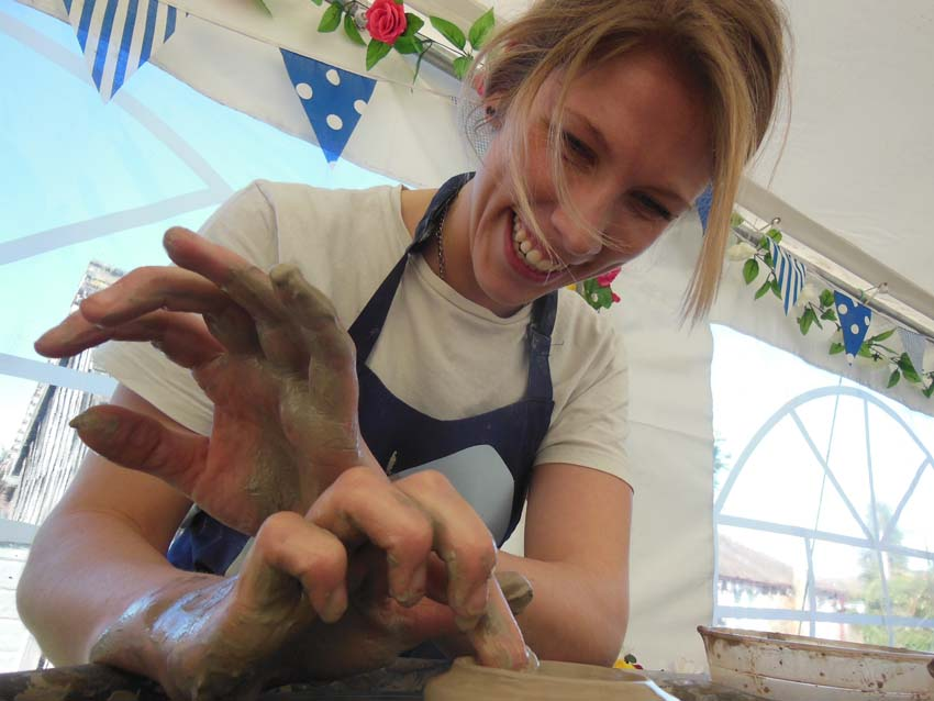 girl laughing making a pot on the potter's wheel at friends pottery hen party