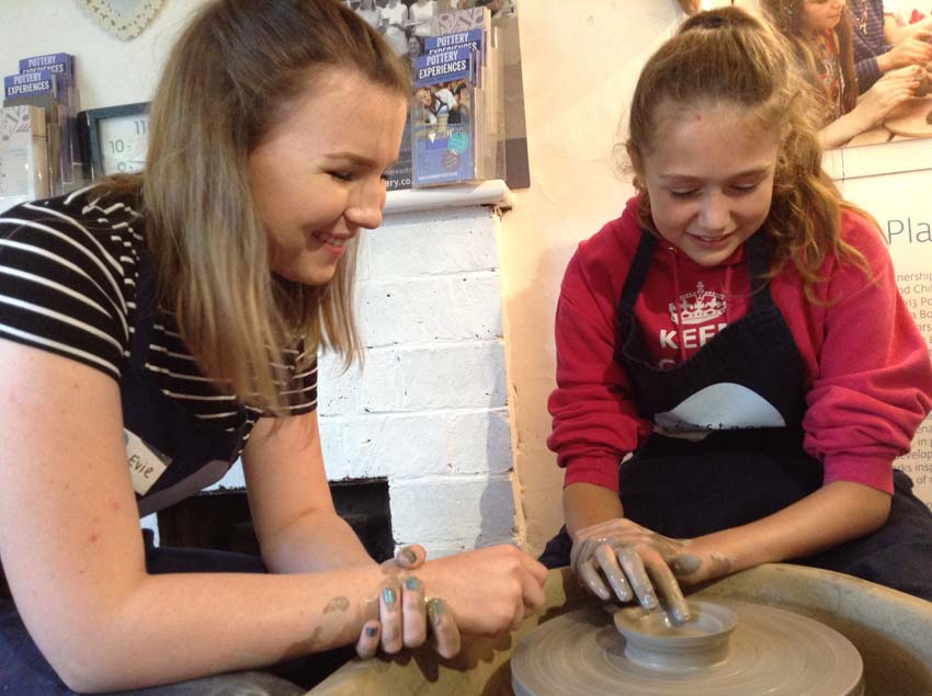 Child receiving potter's wheel tuition at Eastnor Pottery