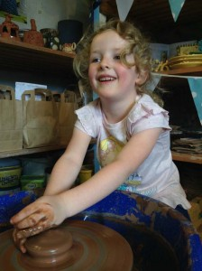 Young girl learning to make pottery on the potter's wheel at Eastnor Pottery