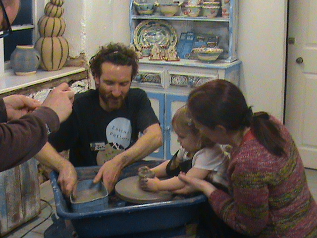Jon the Potter helps a young pottery participant to make a pot on the potter's wheel