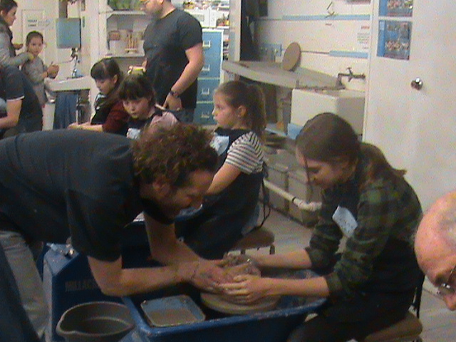 Large family make pots on the potter's wheel